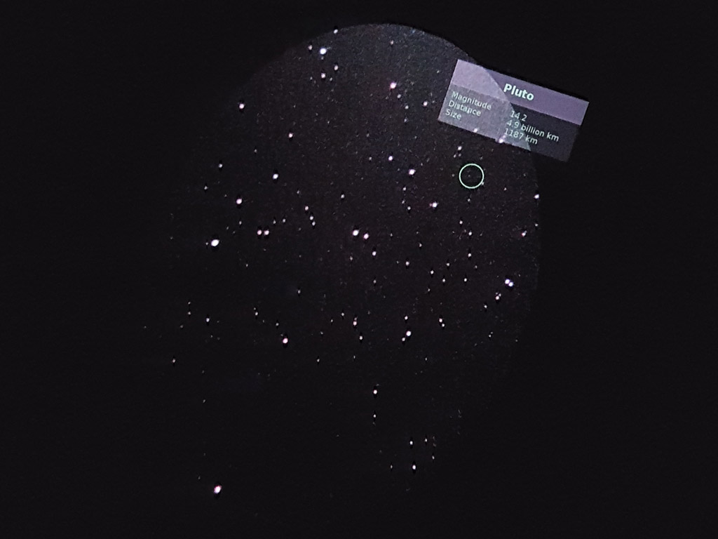 Picture taken with a cellphone in the eyepiece of the telescope. The green circle labels the position of Pluto, which is visible.
